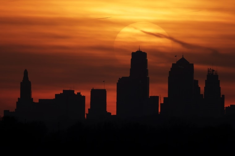 The sun sets behind the downtown Kansas City, Mo. skyline as above average temperatures returned to the region Thursday, March 14, 2013. Government forecasters say much of the United States can expect a warm spring and persistent drought.