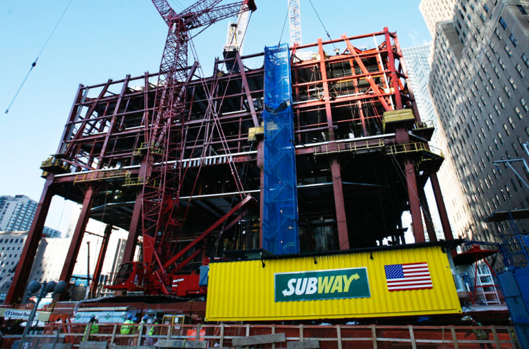 The Subway sandwich shop is hoisted by crane onto the rising steel frame of the Freedom Tower in 2009.