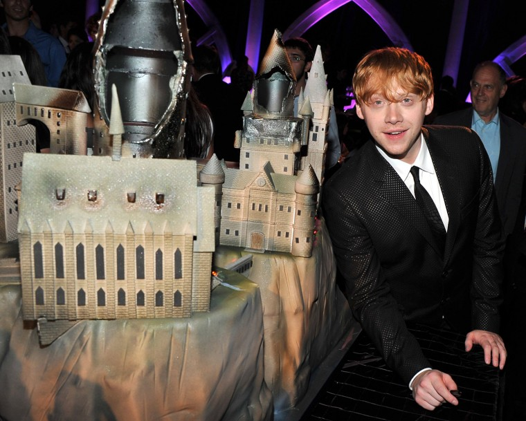 Rupert Grint poses with Charm City's cake creations, at the American Museum of Natural History in New York City.