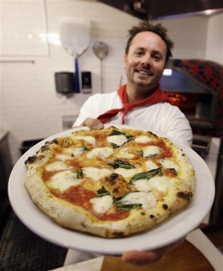 This Thursday, Jan. 27, 2011 photo shows Tony Gemignani as he holds up a pizza margherita at Tony's Pizza Napoletana in San Francisco.