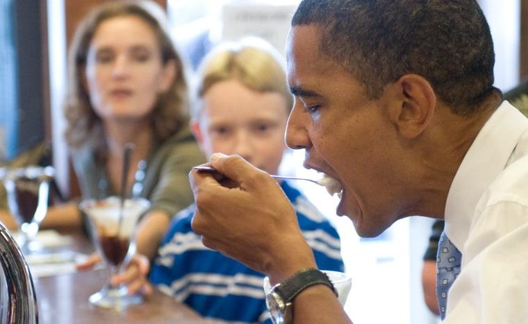 President Obama is shown eating at a milkshake shop.