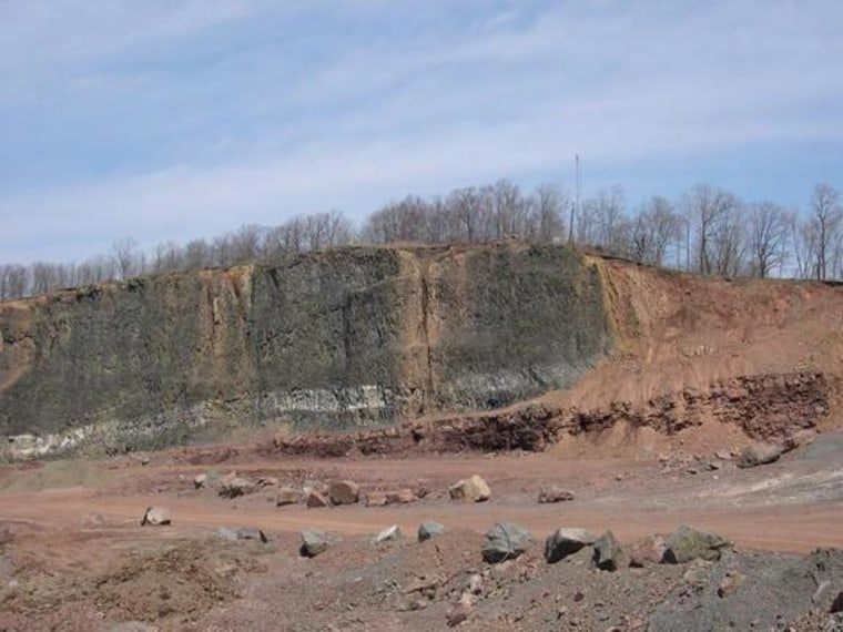 In Clifton, N.J., a massive lava flow (black rock on left) from the time of the End Triassic is exposed in a former quarry. Reddish sedimentary rocks signaling the extinction itself lie to the far right.