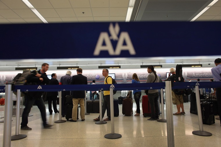 People wait in line at the American Airlines ticket counter in the Miami International Airport on Feb. 12, 2013 in Miami, Fla.