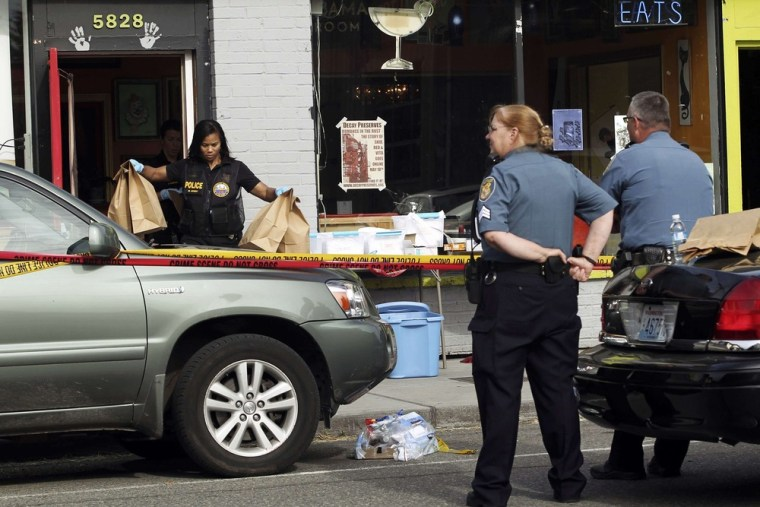 Crime scene investigators remove evidence the scene of a May shooting in Seattle that left six people dead, including the gunman. The Seattle City Council is poised to fund original research into the causes and effects of gun violence.