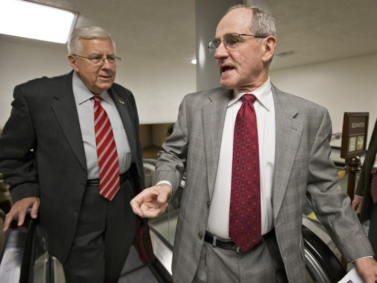 Sen. Jim Risch, R-Idaho, right, turns to Sen. Michael B. Enzi, R-Wyo., as lawmakers rush to the Senate floor on Capitol Hill in Washington, Friday, March 22, 2013, to vote on amendments to the budget resolution.
