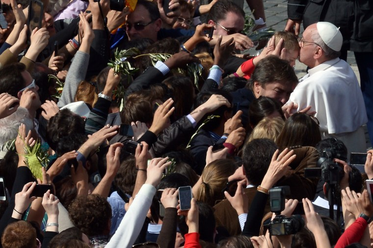 Pope Francis kisses a child after a Mass at the Vatican's St. Peter's Square as part of the Palm Sunday celebration on March 24.
