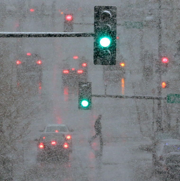 A pedestrian is shrouded in heavy snow as he crosses a downtown street on Saturday, March 23, in Kansas City, Mo.