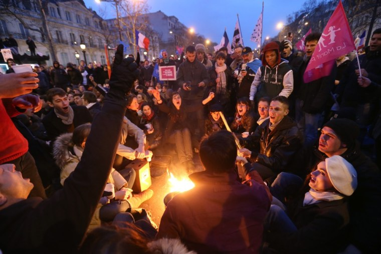Demonstrators sing around a fire during a protest on the Champs-Elysees avenue in Paris on March 24, 2013 against France's gay marriage law in an attempt to block legislation that will allow homosexual couples to marry and adopt children.