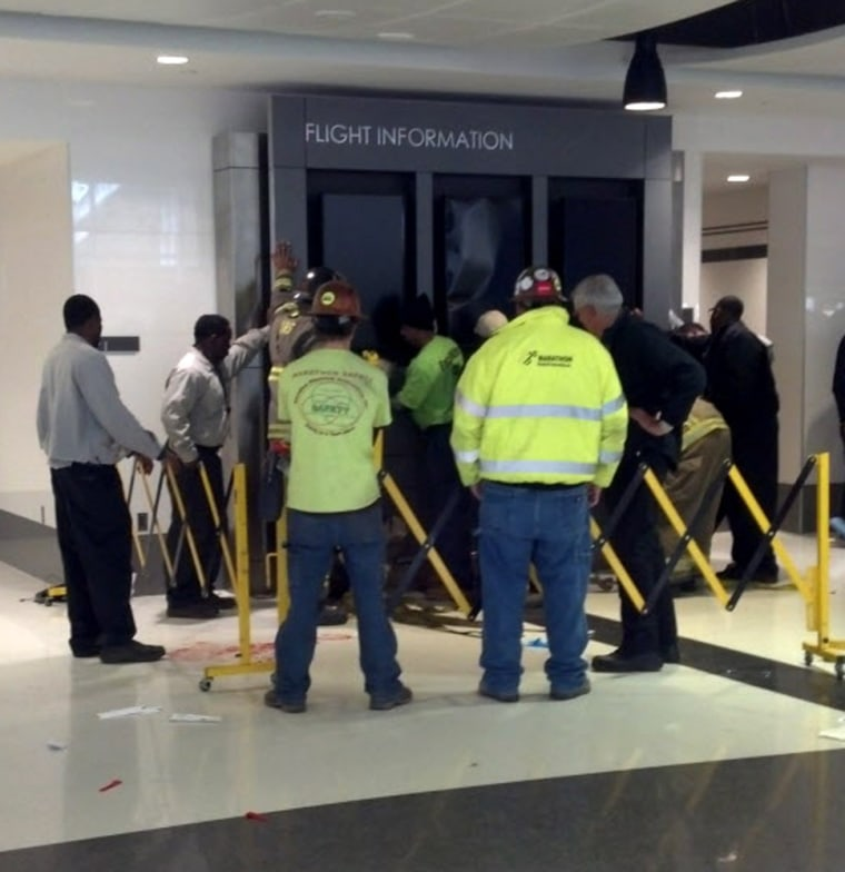 People hold up a flight information sign that fell on a family, killing a boy and injuring mother Heather Bresette and two other sons in Birmingham-Shuttlesworth International Airport on Friday.