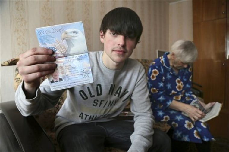 Alexander Abnosov shows his American passport to journalists in the Volga river city of Cheboksary, Russia, on March 20. His 72 -years old grandmother is in the background.