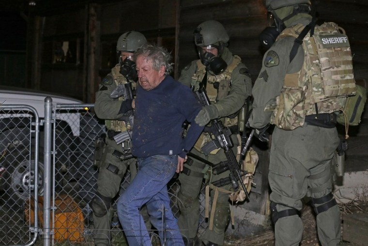 Deputies take Mike McBee into custody in Tacoma, Wash. Tuesday, after he allegedly walked down the street firing guns at houses and then barricaded himself in his home. This photo was provided by the Pierce County Sheriff's Dept.