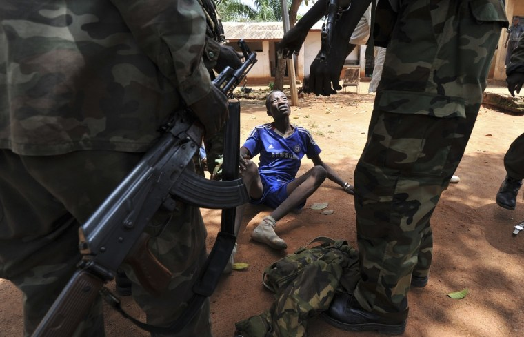 Rebels of the Seleka coalition arrest a man, who was wearing military fatigues and claiming to belong to the Seleka movement, suspected of looting a house in Bangui, Central African Republic, on March 26, 2013.