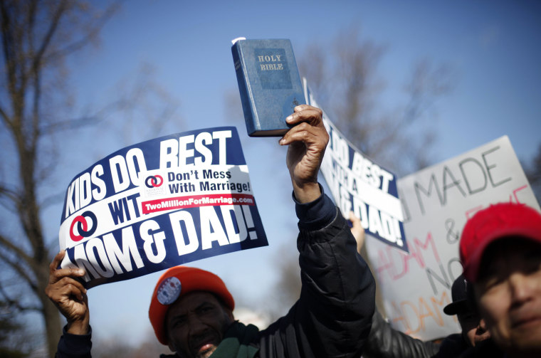 A demonstrator holds a Bible while marching outside the Supreme Court in Washington, on March 26, as the court heard arguments on California's voter approved ban on same-sex marriage, Proposition 8.