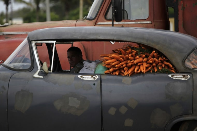 A man sits in a car loaded with carrots at a wholesale market on the outskirts of Havana on March 26.