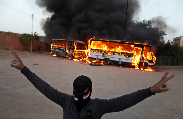 A masked protester flashes the victory sign as he stands in front of burning buses during clashes between supporters and opponents of Egypt's powerful Muslim Brotherhood near the Islamist group's headquarters in Cairo, Egypton March 22, 2013.