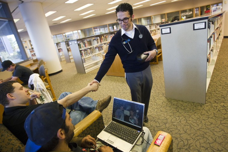 Nurse Daniel Lopez, right, shakes hands as he makes his rounds at a Pima County library branch.