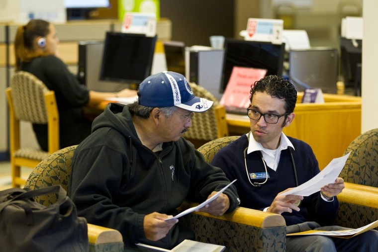 Nurse Daniel Lopez gives Henry Cardoza information on local shelters at the Joel D. Valdez Main Library in Tucson, Ariz.