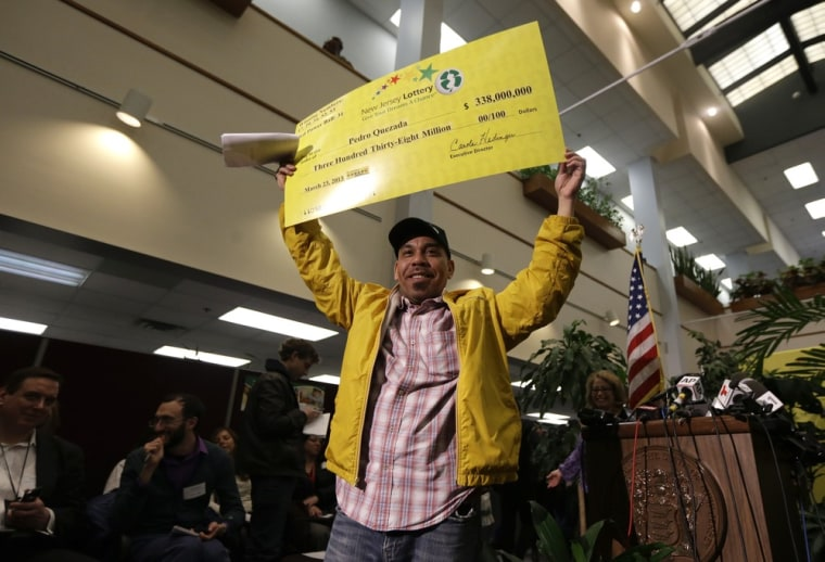 Pedro Quezada, the winner of the Powerball jackpot, holds up a promotional check during a news conference at the New Jersey Lottery headquarters.