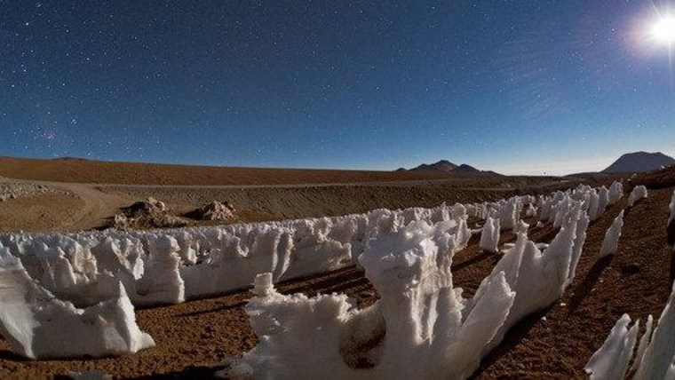These bizarre ice and snow formations are known as penitentes (Spanish for 'penitents'). They are illuminated by the moonlight, which is visible on the right. On the left, higher in the sky, the Large and Small Magellanic Clouds can be faintly seen, while the reddish glow of the Carina Nebula appears close to the horizon on the far left. Photo by ESO Photo Ambassador Babak Tafreshi.