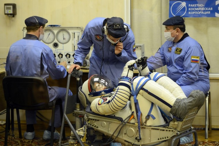 NASA astronaut Christopher Cassidy gets his spacesuit checked prior to Thursday's launch to the International Space Station. Straps bind Cassidy's knees close to his chest, in the position he'll have to maintain during most of the six-hour trip.