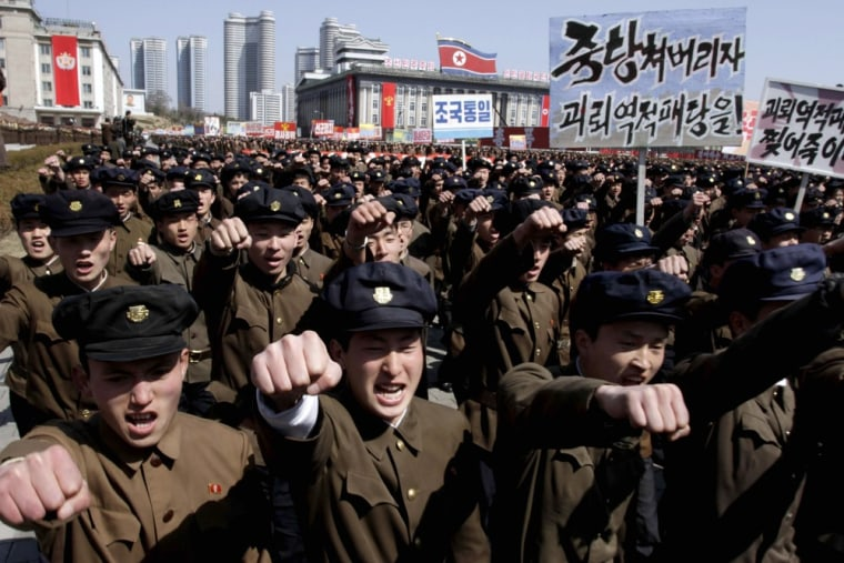 University students punch the air as they march through Kim Il Sung Square in downtown Pyongyang, North Korea, on March 29, 2013.