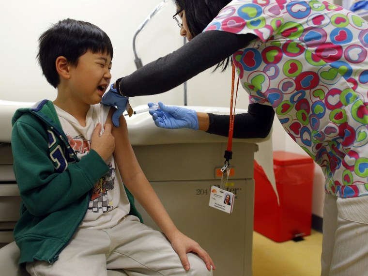 Chihn Ha, 8, gets an influenza vaccine injection from nurse Nho Nguyen, right, during a flu shot clinic at Dorchester House, a health care clinic, in Boston, Mass., in January 2013.