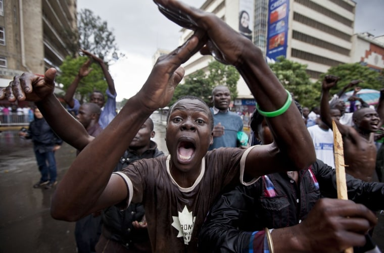 A supporter of losing presidential candidate Raila Odinga gestures as he protests with others in the rain in front of riot police guarding the Supreme Court in Nairobi, Kenya Saturday, March 30, 2013.