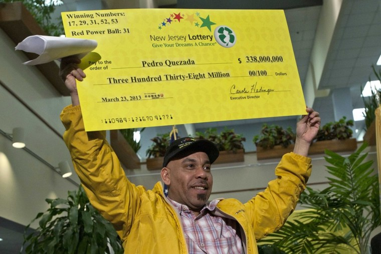 Pedro Quezada holds up the promotional Powerball jackpot check of $338 million at the end of a news conference at the New Jersey Lottery headquarters in Trenton, March 26, 2013.