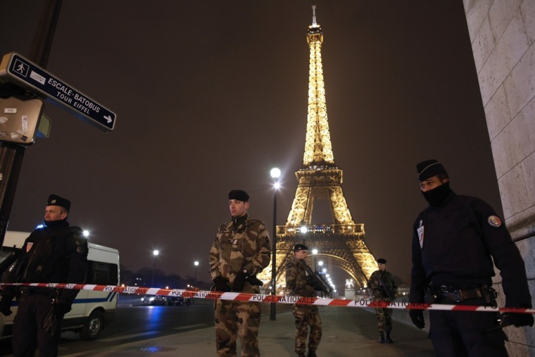 French police stand guard near the Eiffel Tower in Paris on March 30, 2013. The Eiffel Tower was evacuated after an anonymous phone call announced an attack, said a police source. The perimeter of the monument was secured and about 1,400 people were evacuated shortly before 9 p.m.