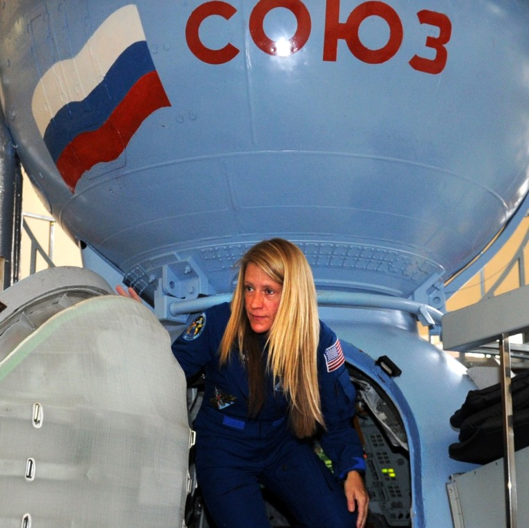 NASA astronaut Karen Nyberg climbs out of a Soyuz spacecraft mock-up at Russia's Star City cosmonaut training center on Tuesday. Nyberg is due to fly to the International Space Station in May, for a fare of $55.8 milllion. That price is rising to $62.7 million in 2016.