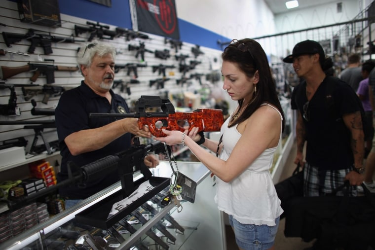 As the U.S. Senate takes up gun legislation in Washington, DC, Dr. Gary Lampert (L), a co-owner of the National Armory gun store, helps Cristiana Ver...