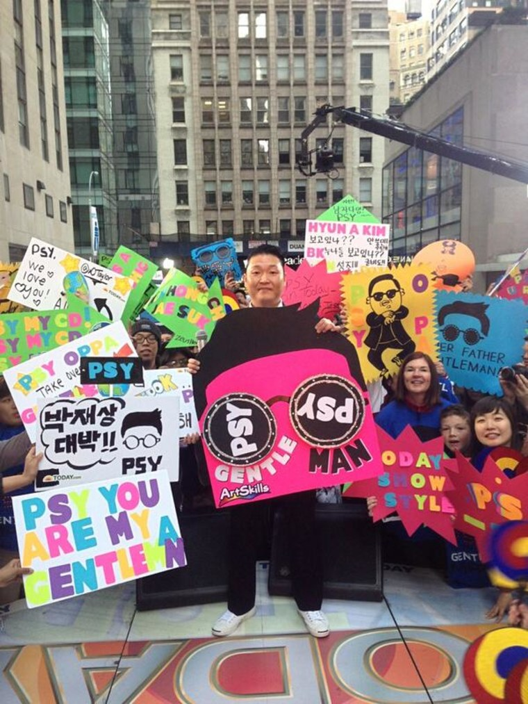 PSY joins his fans on the plaza with their creative signs.