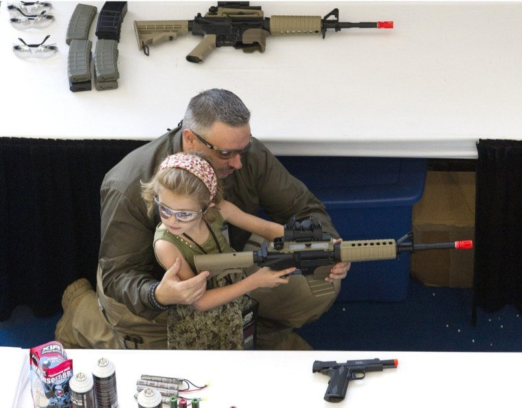 With a little help, a child shoots an Airsoft gun at a target during NRA Youth Day events at the National Rifle Association's 142 Annual Meetings and Exhibits in Houston on Sunday, May 5, 2013..