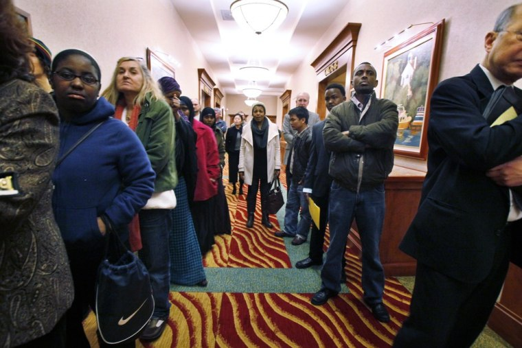 Job seekers line the hall at a job fair in SeaTac, Wash. The number of people requesting unemployment benefits last week dropped slightly, but the fou...