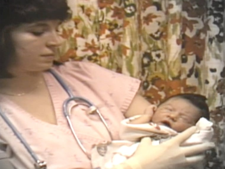 Image: Infant Rachael Clark is held by a medical worker after her rescue