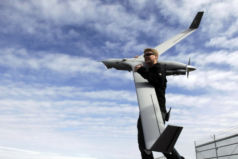 This photo taken March 26, 2013, shows flight test pilot Alex Gustafson carrying an InsituScanEagle unmanned aircraft in preparation for a flight in A...