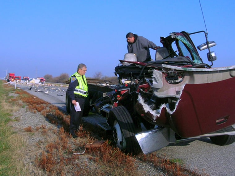 Motor Carrier Inspector Master Trooper Mike Probasco, left, looks over the remains of a box truck with its driver Dagoberto Perez, of Cicero, Ill. in November 2010. Perez, who said he fell asleep and veered off the road, was cited for being a fatigued driver. Both drivers received non-life threatening injuries.