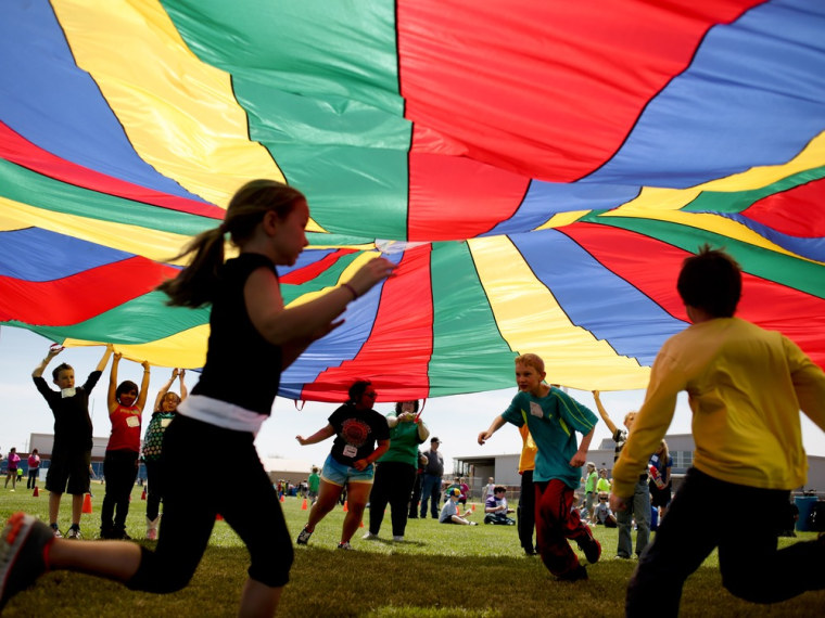 Nickerson Elementary School third grades dash under a rainbow colored tarp before it falls back down on them during the 15th Annual Kansas Kids Fitnes...