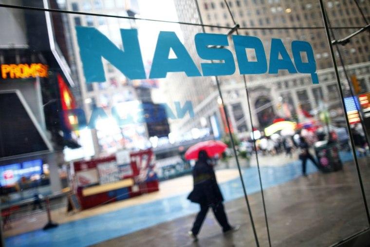 People walk past the NASDAQ MarketSite in New York's Times Square June 4, 2012.