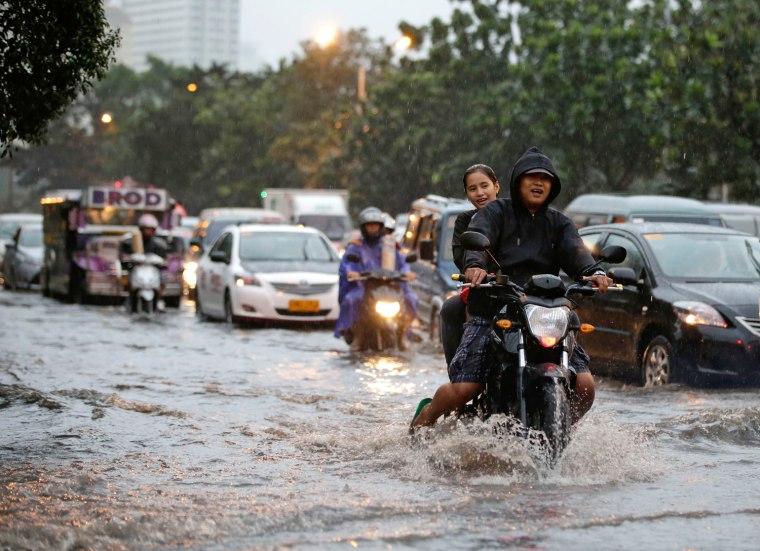 Motorists maneuver through floodwaters following monsoon rains
