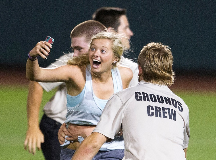 Unidentified female fan is grabbed by stadium security after she ran onto the field during the eighth inning of the 2013 Men's College World Series Fi...