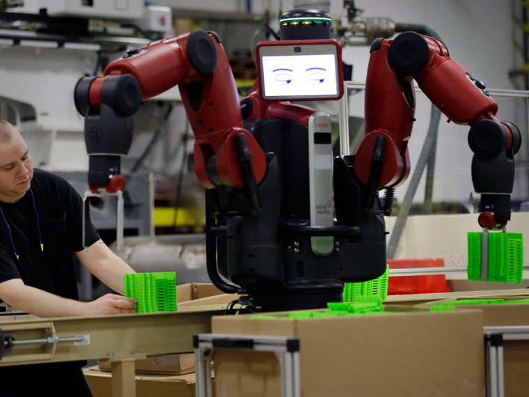 A technician works with Baxter, an adaptive manufacturing robot created by Rethink Robotics at The Rodon Group manufacturing facility, Tuesday, March ...