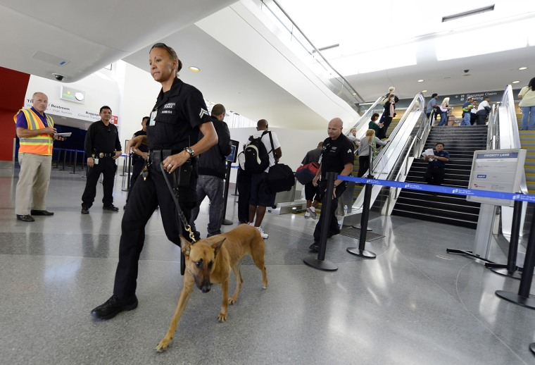 A Los Angeles Police Department officer and her canine leave after making a sweep of the re-opened Terminal 3 on Nov. 2, one day after a shooting at Los Angeles International Airport.