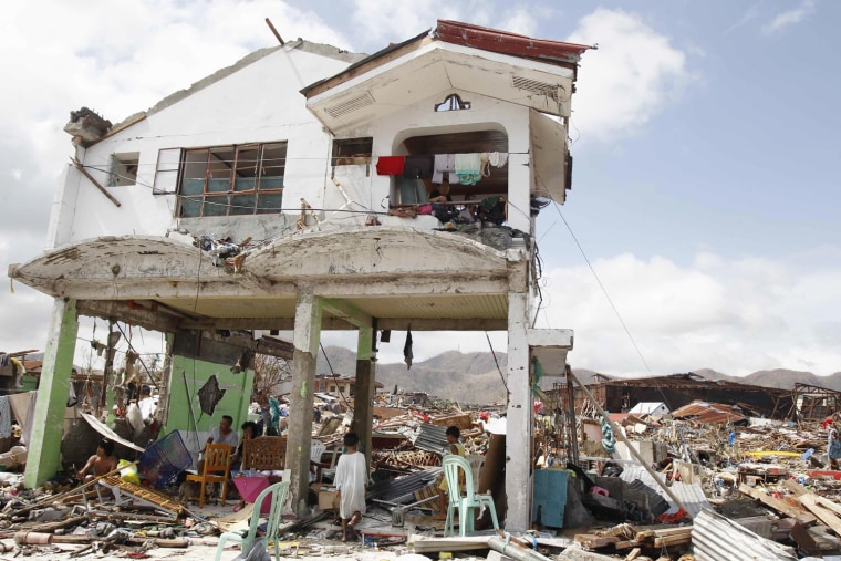 Survivors stay in their damaged house after Super Typhoon Haiyan battered Tacloban city, central Philippines.
