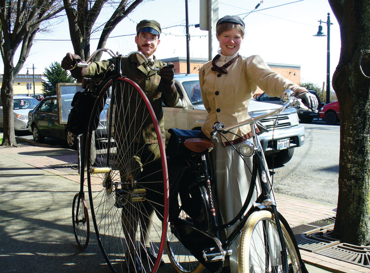 Chrisman and her husband in Victorian-era attire, riding bicycles of the period.