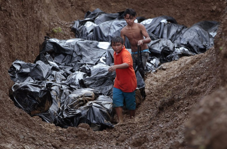 Philippine workers fight the clock to name dead while digging mass graves