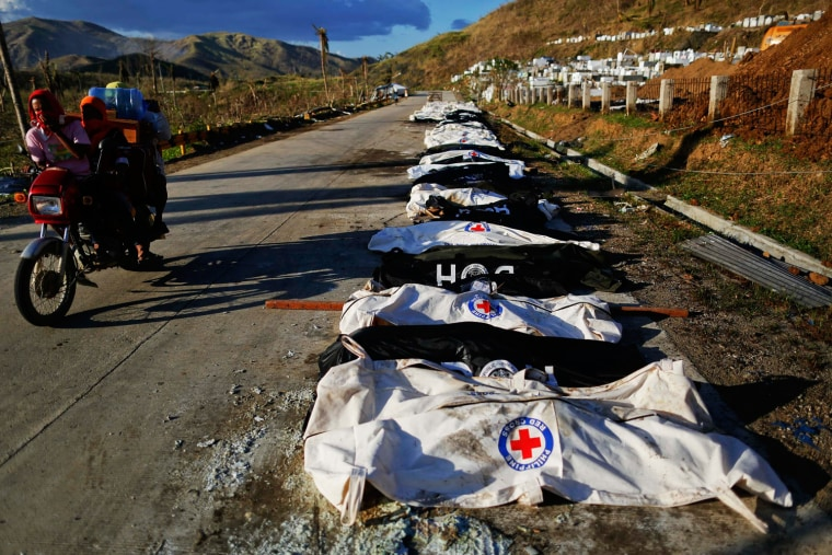 People cover their noses from the stench as they ride past a mass grave with more than 700 bodies of victims of Typhoon Haiyan just outside Tacloban, the Philippines, on Monday.