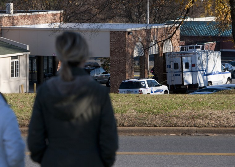 Liberty University students watch as police investigate a fatal shooting at an off-campus women's dormitory in Lynchburg, Va.