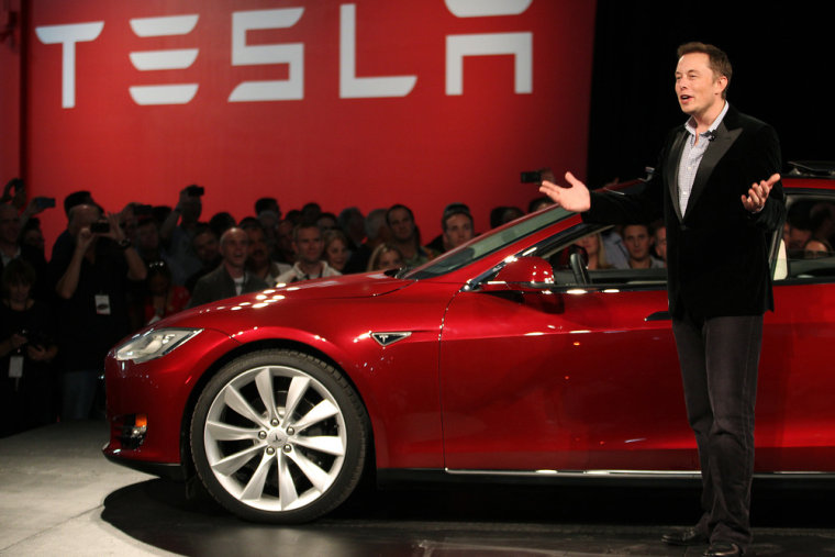 Tesla Motors CEO Elon Musk speaks next to the company's newest Model S during the Model S Beta Event held at the Tesla factory in Fremont, California ...
