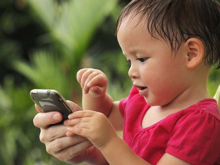 young girl playing with phone, msnbc.com, stock, photography, child, kid, text, texting,